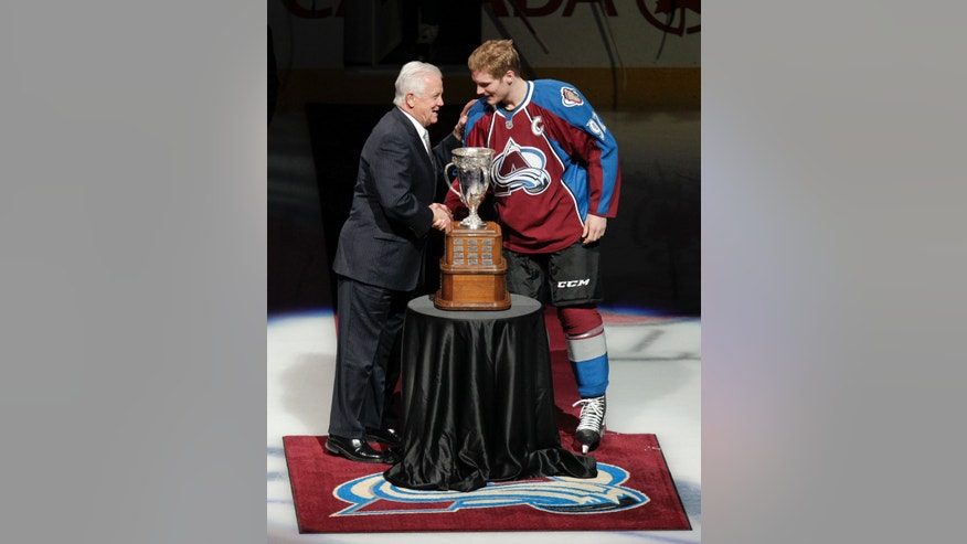 Former NHL player Ralph Backstrom, left, awards the Calder Trophy to Colorado Avalanche's Gabriel Landeskog, right, of Sweden, the 2012 NHL rookie of the year, before an NHL hockey between the Avalanche and the Los Angeles Kings on Tuesday, Jan. 22, 2013, in Denver. Backstrom won the award in 1959. (AP Photo/Barry Gutierrez)
