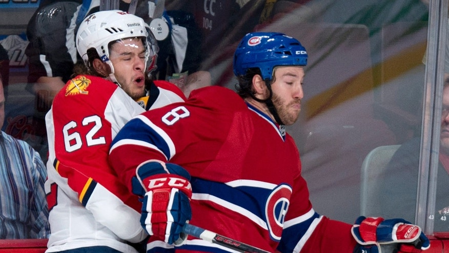 Florida Panthers' Michael Caruso (62) reacts as he is checked into the boards by Montreal Canadiens' Brandon Prust during the first period of their NHL hockey game, Tuesday, Jan. 22, 2013, in Montreal. (AP Photo/The Canadian Press, Paul Chiasson)