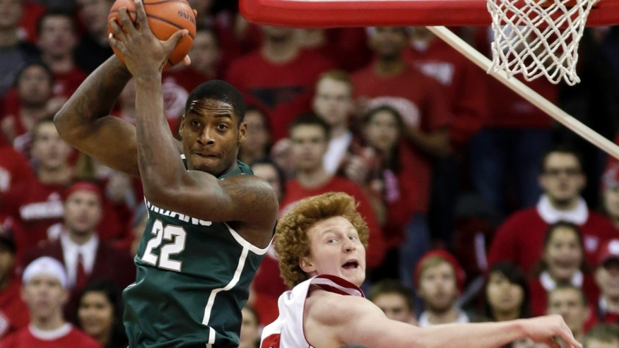 Michigan State's Branden Dawson (22) pulls a defensive rebound away from Wisconsin's Mike Bruesewitz during the first half of an NCAA college basketball game Tuesday, Jan. 22, 2013, in Madison, Wis. (AP Photo/Andy Manis)