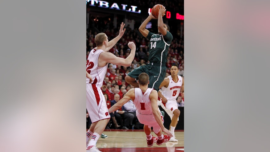 Michigan State's Gray Harris (14) shoots against Wisconsin's Evan Anderson, left, and Ben Brust (1) during the first half of an NCAA college basketball game Tuesday, Jan. 22, 2013, in Madison, Wis. (AP Photo/Andy Manis)