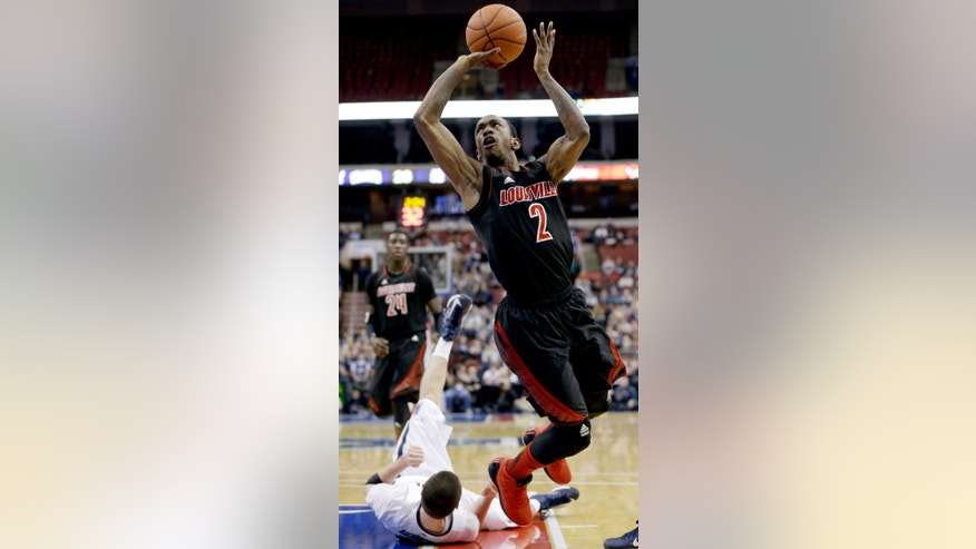 Louisville's Russ Smith (2) shoots after knocking over Villanova's Ryan Arcidiacono during the first half of an NCAA college basketball game, Tuesday, Jan. 22, 2013, in Philadelphia. (AP Photo/Matt Slocum)