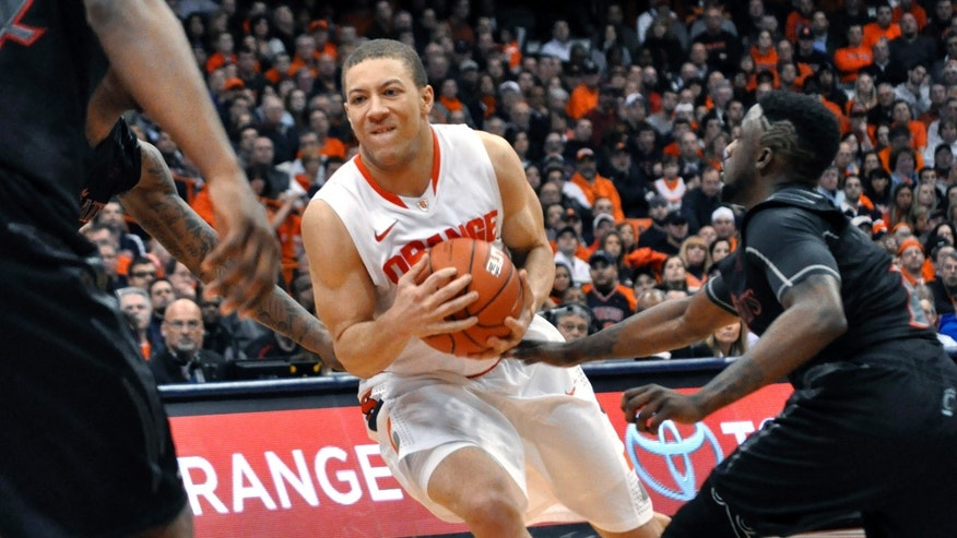 Syracuse's Brandon Triche tries to take the ball to the basket past Cincinnati's Cashmere Wright during the second half of an NCAA college basketball game in Syracuse, N.Y., Monday, Jan. 21, 2013. Syracuse won 57-55. (AP Photo/Kevin Rivoli)