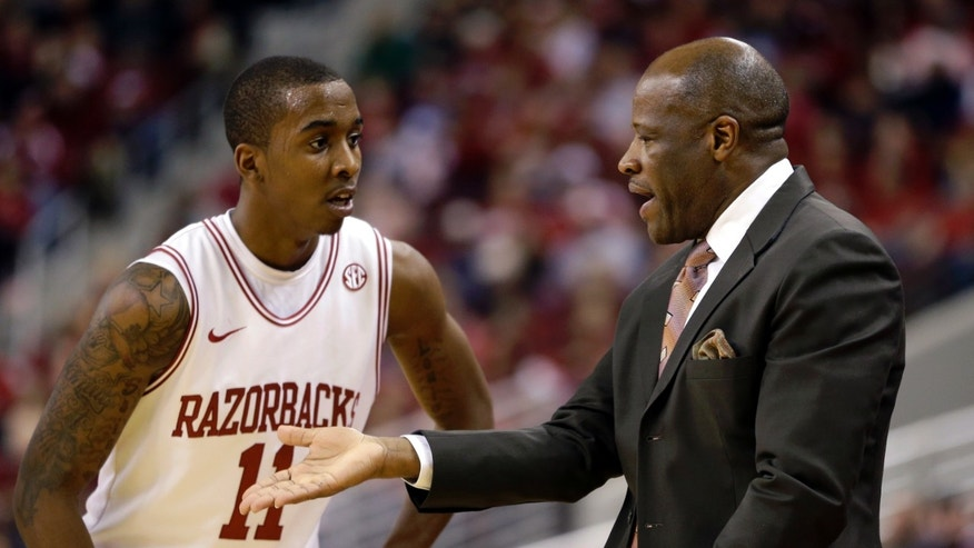 FILE - In this Dec. 22, 2012, file photo, Arkansas coach Mike Anderson, right, talks to BJ Young during the first half of an NCAA college basketball game in North Little Rock, Ark. Young is once again Arkansas' leading scorer this season, but his shooting percentages are down across the board. The sophomore has made up for his shooting woes, however, by evolving into the overall playmaker coach Anderson was looking for. (AP Photo/Daniel Johnston, File)