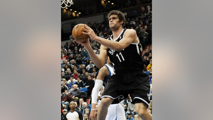 Brooklyn Nets' Brook Lopez looks to pass in the second half of an NBA basketball game against the Minnesota Timberwolves, Wednesday, Jan. 23, 2013, in Minneapolis.  Lopez led the the Nets with 22 points and 7 rebounds in their 91-83 win. (AP Photo/Jim Mone)