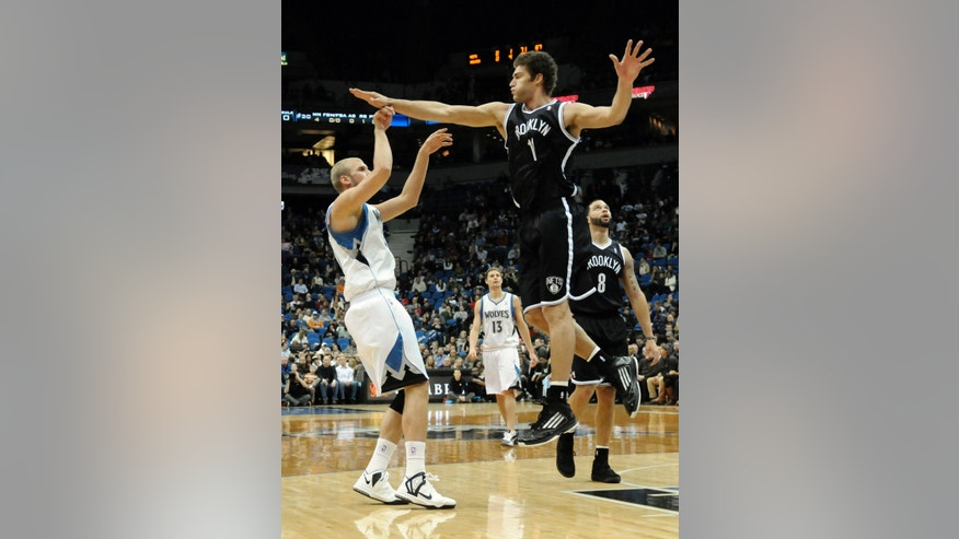 Brooklyn Nets' Brook Lopez, right, hits Minnesota Timberwolves' Greg Stiemsma's hand while trying to block a shot in the first half of an NBA basketball game on Wednesday, Jan. 23, 2013, in Minneapolis. (AP Photo/Jim Mone)