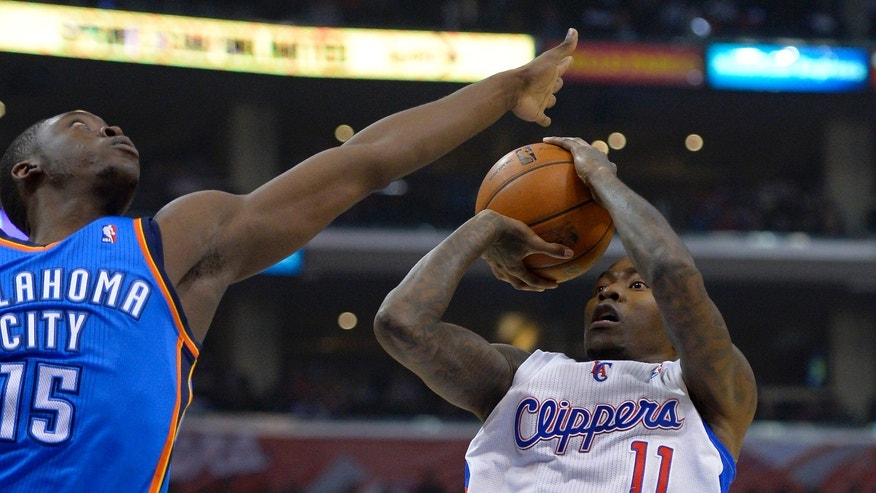 Los Angeles Clippers guard Jamal Crawford, right, puts up a shot as Oklahoma City Thunder guard Reggie Jackson defends during the first half of their NBA basketball game, Tuesday, Jan. 22, 2013, in Los Angeles.  (AP Photo/Mark J. Terrill)
