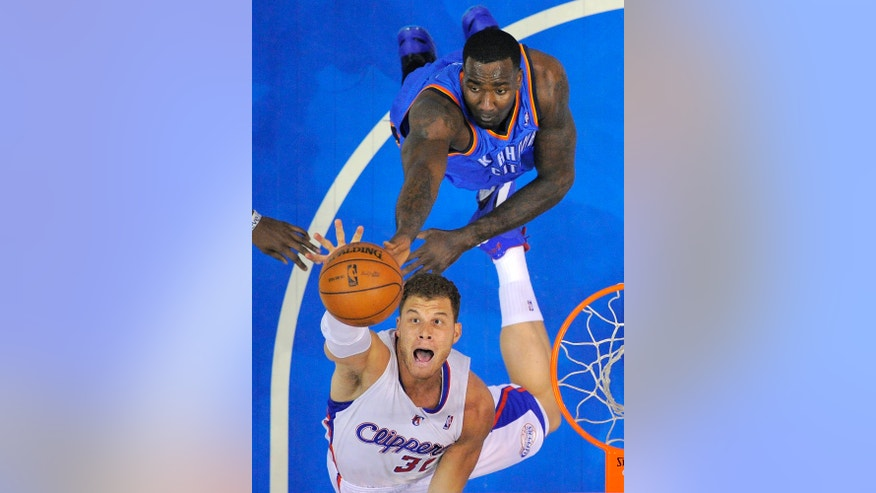 Los Angeles Clippers forward Blake Griffin, below, goes after a rebound along with Oklahoma City Thunder center Kendrick Perkins during the first half of their NBA basketball game, Tuesday, Jan. 22, 2013, in Los Angeles.  (AP Photo/Mark J. Terrill)