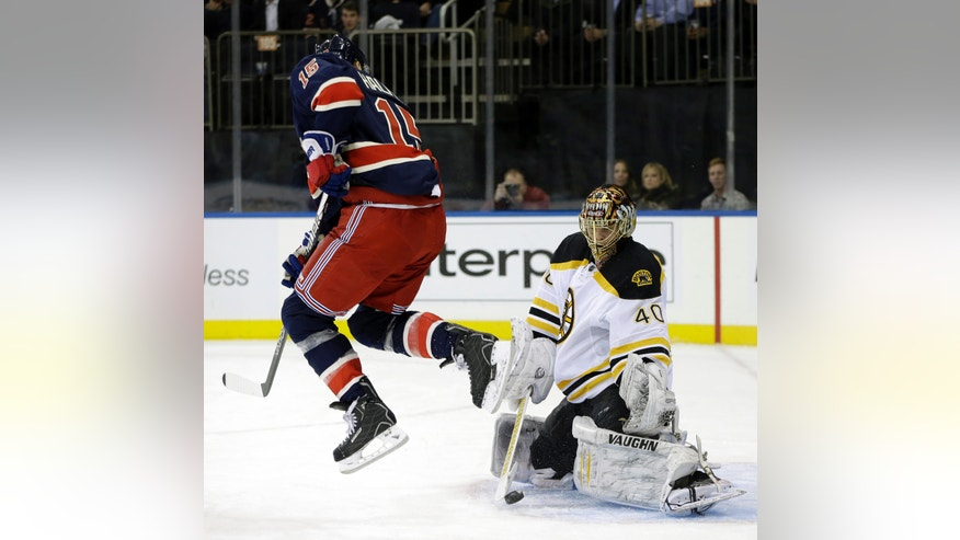 New York Rangers center Jeff Halpern (15) leaps to allow the puck through as Boston Bruins goalie Tuukka Rask (40) makes a save in the second period of their NHL hockey game at Madison Square Garden in New York, Wednesday, Jan. 23, 2013.  (AP Photo/Kathy Willens)