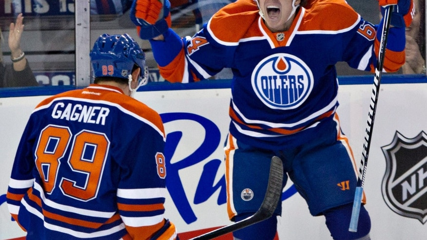 Edmonton Oilers' Nail Yakupov, 64, celebrates his first NHL with teammate Sam Gagner against the San Jose Sharks during first period NHL hockey action in Edmonton, Alberta, on Tuesday Jan. 22, 2013. (AP Photo/The Canadian Press, Jason Franson)