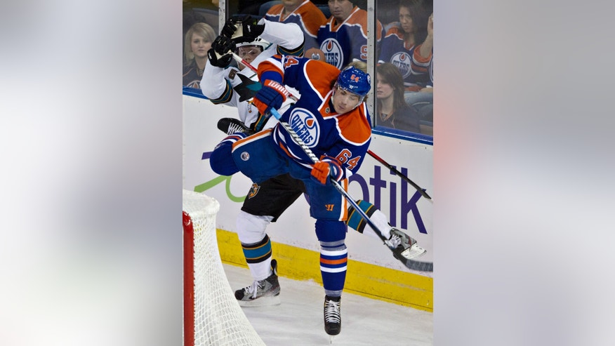 San Jose Sharks' Matthew Irwin, left, and Edmonton Oilers' Nail Yakupov collide behind the net during second period NHL hockey action in Edmonton, Alberta, on Tuesday Jan. 22, 2013. (AP Photo/The Canadian Press, Jason Franson)