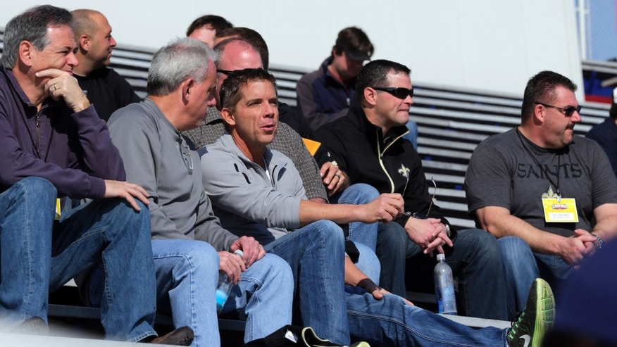 New Orleans Saints coach Sean Payton, center, talks with assistant head coach Joe Vitt, second from left, during Senior Bowl football practice at Ladd-Peebles Stadium in Mobile, Ala., Wednesday, Jan. 23, 2013. The NFL reinstated Payton on Tuesday following a season long suspension. Vitt served has head coach during the suspension. (AP Photo/Dave Martin)