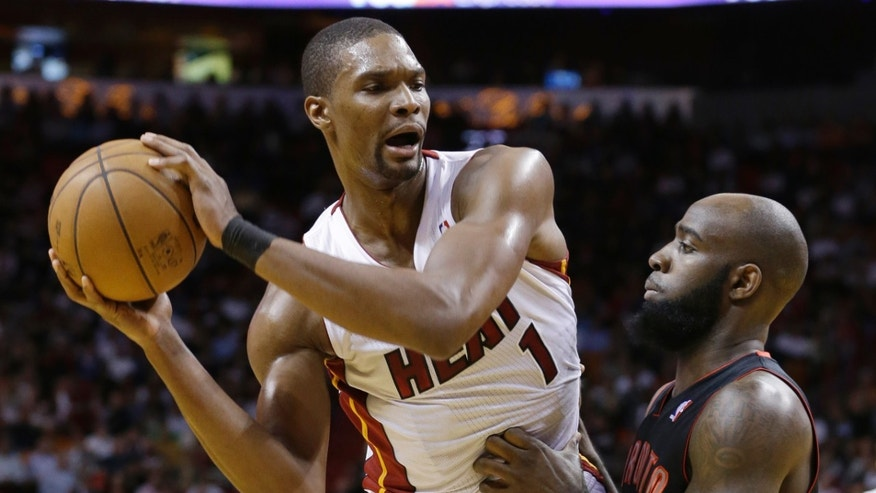 Miami Heat center Chris Bosh (1) looks for an opening past Toronto Raptors forward Quincy Acy during the first half of an NBA basketball game on Wednesday, Jan. 23, 2013, in Miami. (AP Photo/Wilfredo Lee)
