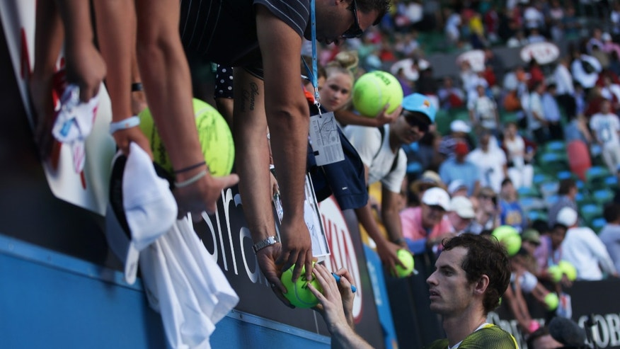 Britain's Andy Murray signs autographs after winning his quarterfinal match against France's Jeremy Chardy at the Australian Open tennis championship in Melbourne, Australia, Wednesday, Jan. 23, 2013. (AP Photo/Dita Alangkara)