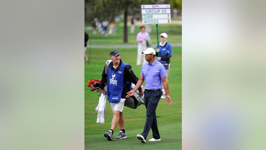 Tiger Woods, right, talks with his caddie Joe LaCava, left, during his round in the Pro-Am at the Farmers Insurance Open golf tournament at Torrey Pines on Wednesday, Jan 23, 2013 in San Diego.  (AP Photo/Denis Poroy)