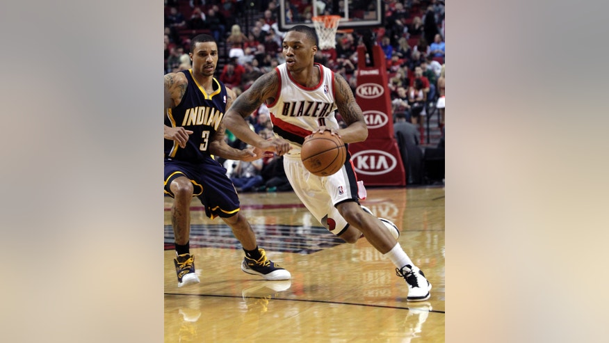 Portland Trail Blazers guard Damian Lillard, right, drives on Indiana Pacers guard George Hill during the first quarter of an NBA basketball game in Portland, Ore., Wednesday, Jan. 23, 2013. (AP Photo/Don Ryan)
