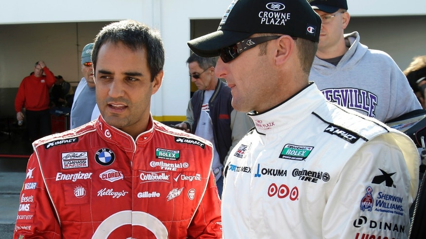 Juan Pablo Montoya, left, of Colombia, and Joey Hand talk in the garage area after a practice session for the Rolex 24 hour auto race at Daytona International Speedway, Thursday, Jan. 24, 2013, in Daytona Beach, Fla. (AP Photo/John Raoux)