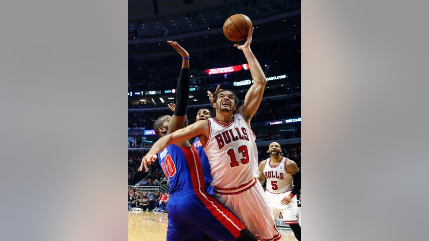 Chicago Bulls center Joakim Noah (13) shoots over Detroit Pistons center Greg Monroe (10) during the first half of an NBA basketball game, Wednesday, Jan. 23, 2013, in Chicago. (AP Photo/Charles Rex Arbogast)