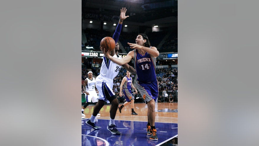 Phoenix Suns forward Luis Scola, of Argentina, right, goes to the basket against Sacramento Kings forward Jason Thompson during the first quarter of an NBA basketball game in Sacramento, Calif., Wednesday, Jan. 23, 2013. (AP Photo/Rich Pedroncelli)