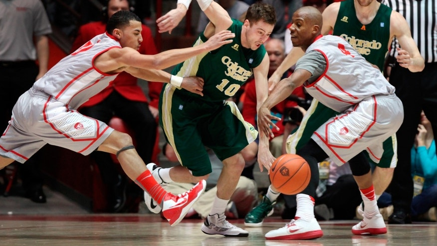 Colorado State's Wes Eikmeier (10) fights through the defense of New Mexico's Kendall Williams, left, and Chad Adams in the first half of their NCAA basketball game in Albuquerque, N.M., Wednesday, Jan. 23, 2013. Colorado State's Pierce Hornung, behind right, watches the play. (AP Photo/Eric Draper)