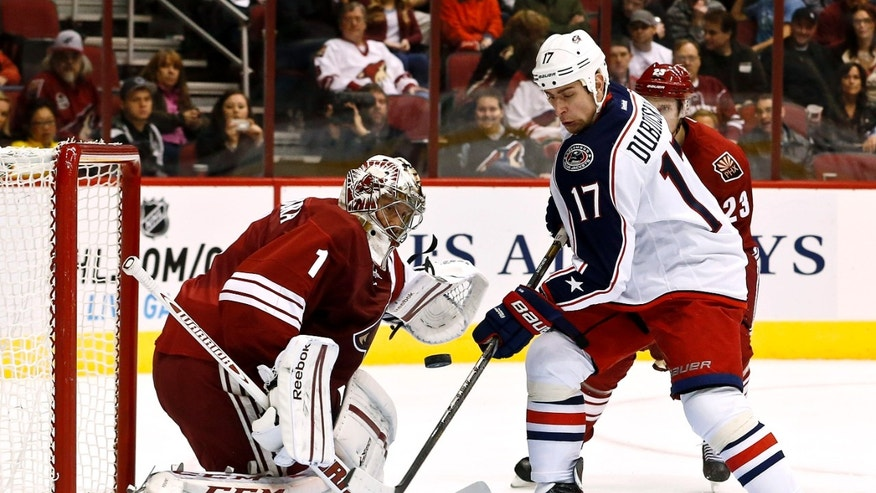 Columbus Blue Jackets' Brandon Dubinsky (17) tries to control the puck to get a shot on goal as Phoenix Coyotes' Jason LaBarbera (1) moves in to make a save during the second period in an NHL hockey game, Wednesday, Jan. 23, 2013, in Glendale, Ariz. (AP Photo/Ross D. Franklin)