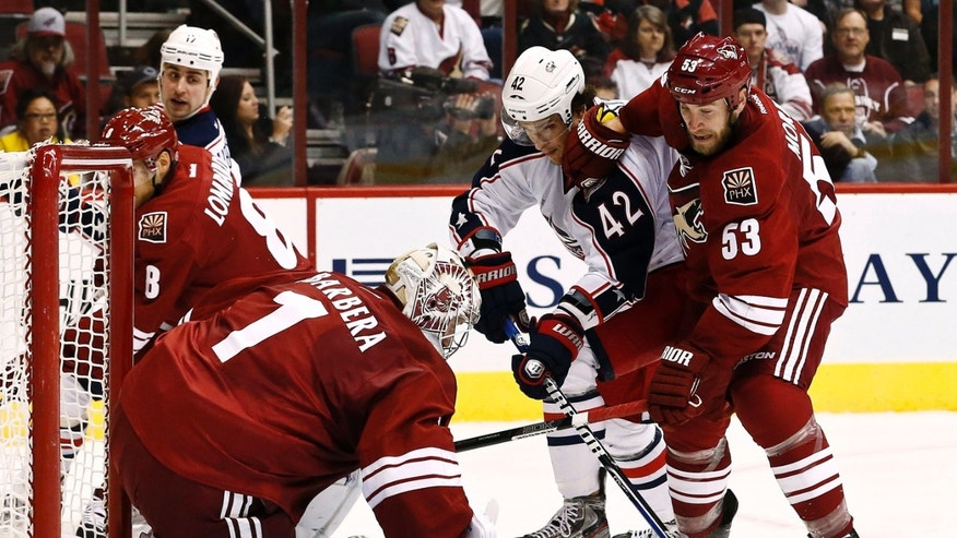 Phoenix Coyotes goalie Jason LaBarbera (1) makes a save on a shot by Columbus Blue Jackets' Artem Anisimov (42), of Russia, as Coyotes' Derek Morris (53) defends during the second period in an NHL hockey game, Wednesday, Jan. 23, 2013, in Glendale, Ariz. (AP Photo/Ross D. Franklin)