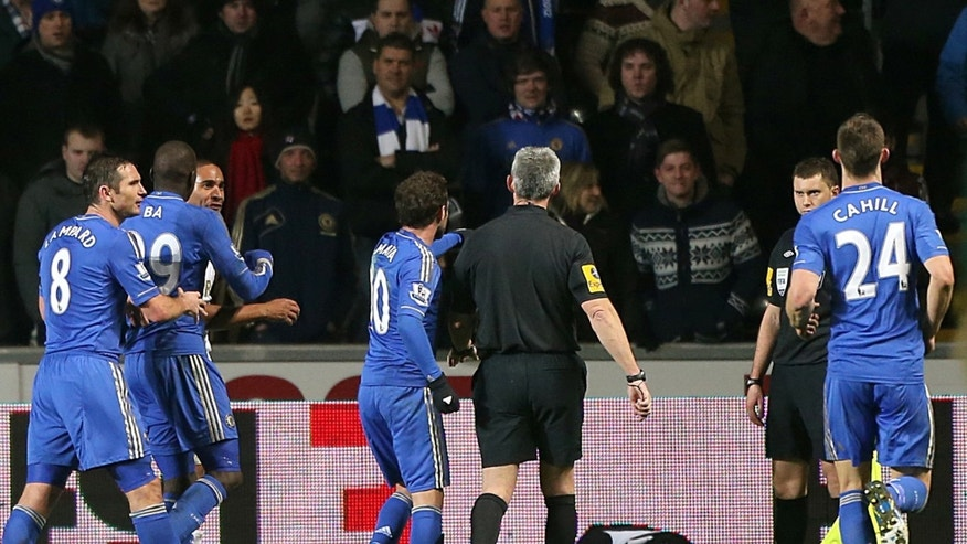 A ball boy, third right, lies on the pitch following an incident Chelsea's Eden Hazard, not pictured,  as referee Chris Foy, center in black, makes his way over to calm the situation during the English League Cup second leg semi-final soccer match between Chelsea and Swansea City at the Liberty Stadium, Swansea, Wales, Wednesday Jan. 23, 2013.  Hazard received a red card for the incident. (AP Photo/PA, Nick Potts) UNITED KINGDOM OUT  NO SALES  NO ARCHIVE