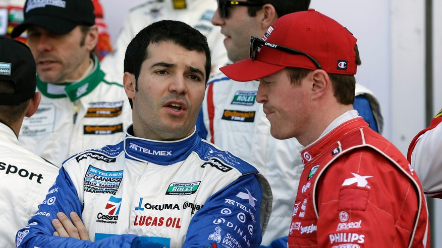 Memo Rojas, left, of Mexico, talks with Scott Dixon, of New Zealand, after their practice session for the Rolex 24 hour auto race at Daytona International Speedway, Friday, Jan. 25, 2013, in Daytona Beach, Fla. (AP Photo/John Raoux)