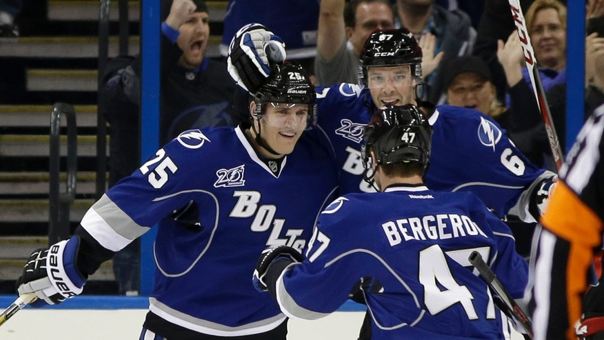 Tampa Bay Lightning defenseman Matt Carle (25) celebrates with left wing Benoit Pouliot (67) and defenseman Marc-Andre Bergeron (47) after scoring against the Ottawa Senators during the first period of an NHL hockey game Friday, Jan. 25, 2013, in Tampa, Fla. (AP Photo/Chris O'Meara)