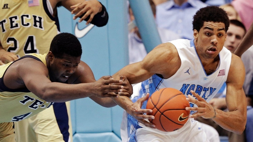 Georgia Tech's Robert Carter (4) grabs North Carolina's James Michael McAdoo during the second half of an NCAA college basketball game in Chapel Hill, N.C., Wednesday, Jan. 23, 2013. North Carolina won 79-63. (AP Photo/Gerry Broome)