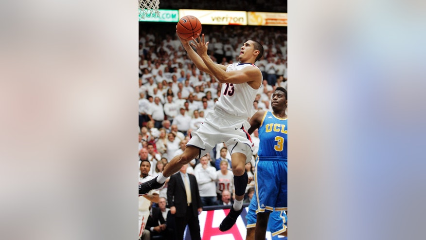 Arizona's Nick Johnson (13) shoots past UCLA's Jordan Adams (3) during the first half of an NCAA college basketball game in Tucson, Ariz., Thursday, Jan. 24, 2013. (AP Photo/John Miller)