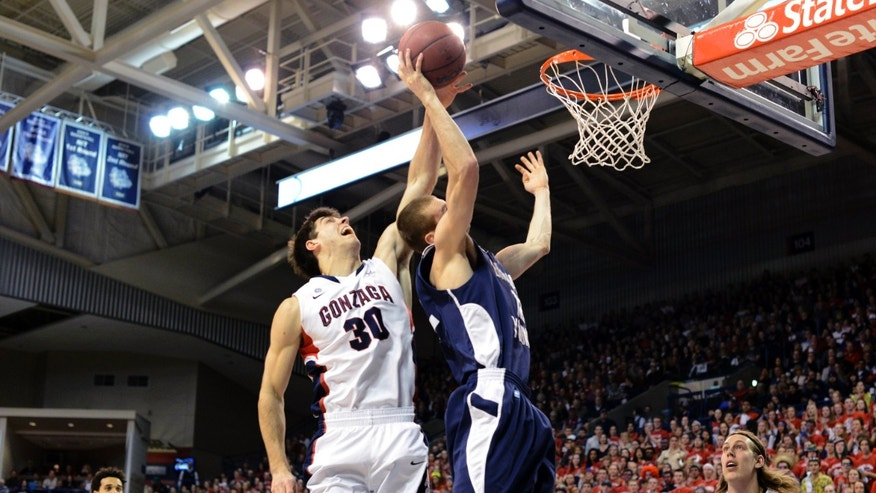 Bringham Youngs's Josh Sharp is blocked by Gonzaga's Mike Hart (30) as Elias Harris, left, and Kelly Olynyk watch in the first half of an NCAA college basketball game, Thursday, Jan. 24, 2013, in Spokane, Wash. (AP Photo/Jed Conklin)