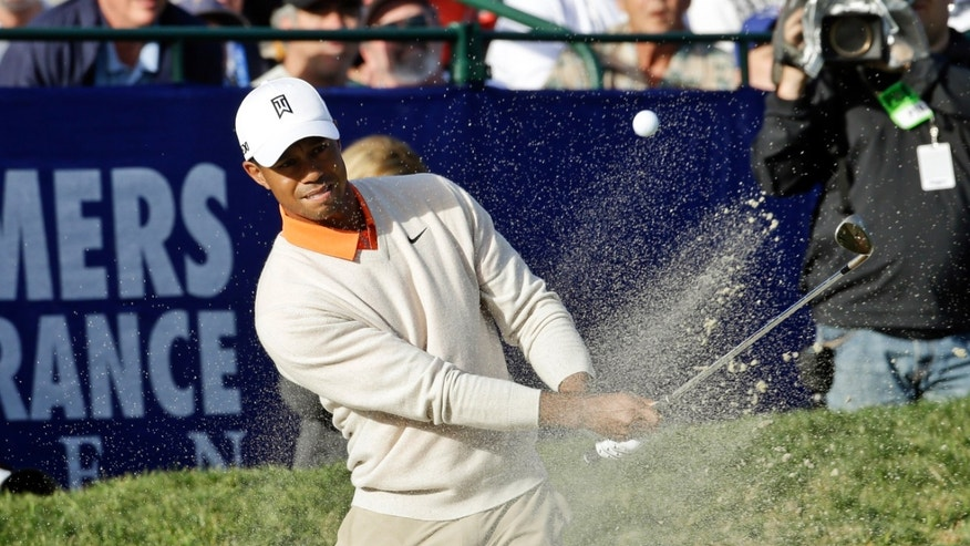 Tiger Woods hits from the bunker behind the 18th green of the South Course at Torrey Pines during the first round of the Farmers Insurance Open golf tournament, Thursday, Jan. 24, 2013, in San Diego. (AP Photo/Lenny Ignelzi)