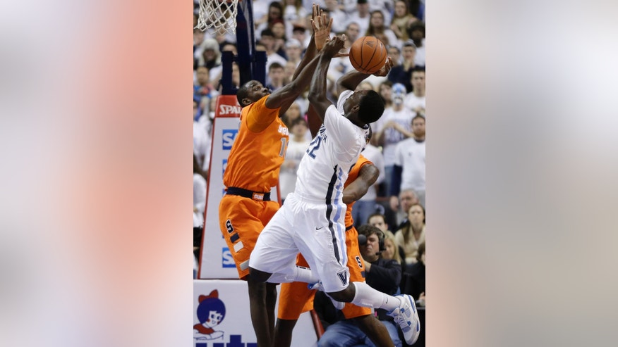 Villanova's JayVaughn Pinkston, right, has his shot blocked by Syracuse's Baye Keita during the first half of an NCAA college basketball game, Saturday, Jan. 26, 2013, in Philadelphia. (AP Photo/Matt Slocum)