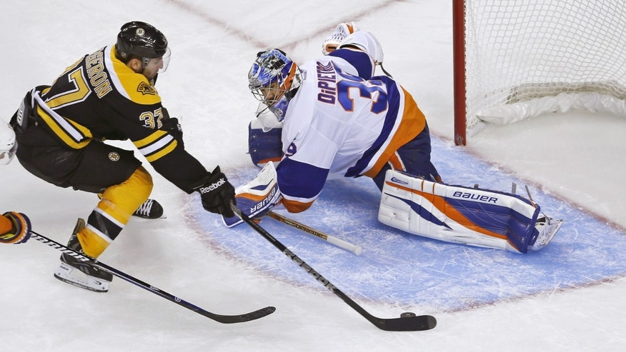 Boston Bruins center Patrice Bergeron (37) breaks past New York Islanders goalie Rick DiPietro (39) for a goal during the third period of an NHL hockey game in Boston, Friday, Jan. 25, 2013. (AP Photo/Charles Krupa)