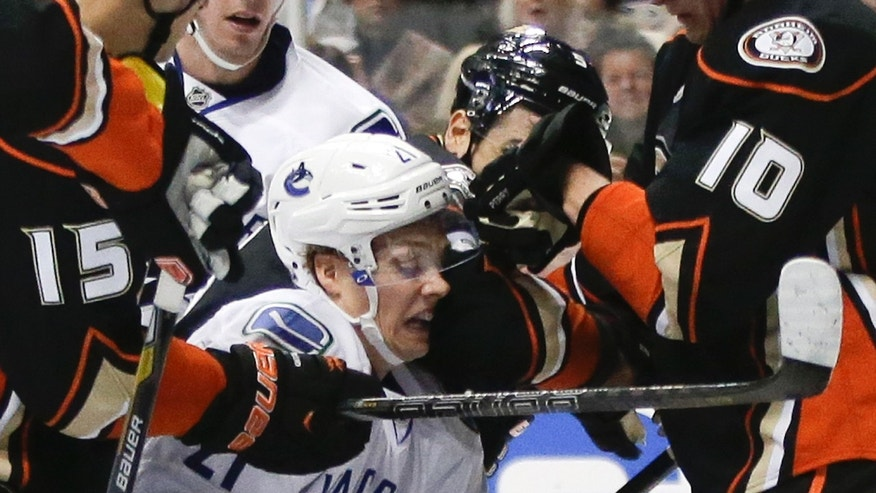 Vancouver Canucks left wing Mason Raymond is high-sticked by Anaheim Ducks defenseman Luca Sbisa, rear, during the first period of an NHL hockey game in Anaheim, Calif., Friday, Jan. 25, 2013. (AP Photo/Chris Carlson)