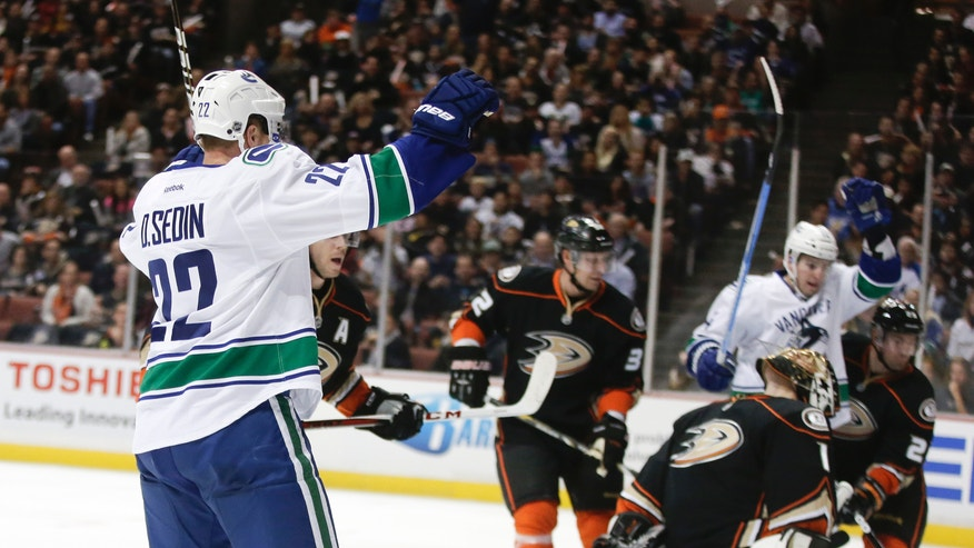 Vancouver Canucks left wing Daniel Sedin, left, celebrates his goal past Anaheim Ducks goalie Jonas Hiller during the first period of an NHL hockey game in Anaheim, Calif., Friday, Jan. 25, 2013. (AP Photo/Chris Carlson)
