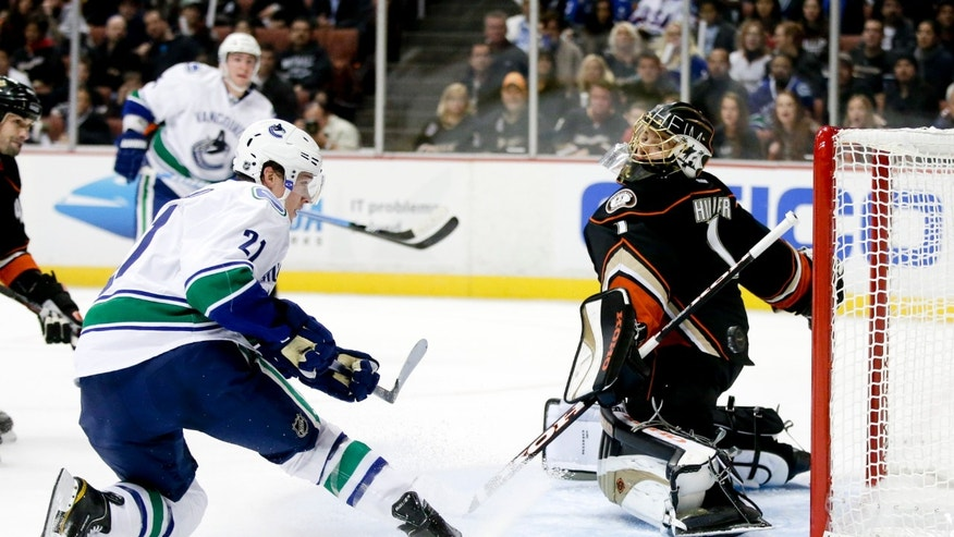 Vancouver Canucks left wing Mason Raymond, left front, scores past Anaheim Ducks goalie Jonas Hiller during the first period of an NHL hockey game in Anaheim, Calif. Friday, Jan. 25, 2013. (AP Photo/Chris Carlson)