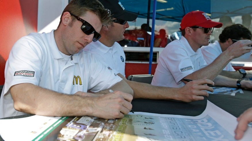 Ganassi Racing team drivers from left, Jamie McMurray, Joey Hand and Scott Dixon, of New Zealand, sign autographs for fans prior to the start of the Grand-Am Series Rolex 24 hour auto race at Daytona International Speedway, Saturday, Jan. 26, 2013, in Daytona Beach, Fla. (AP Photo/John Raoux)