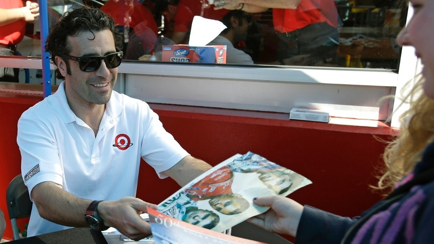 Dario Franchitti, of Scotland, hands a signed poster to a race fan in the garage area prior to the start of the Grand-Am Series Rolex 24 hour auto race at Daytona International Speedway, Saturday, Jan. 26, 2013, in Daytona Beach, Fla. (AP Photo/John Raoux)