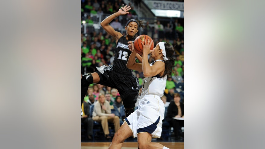 Notre Dame guard Skylar Diggins, right, scores her 2,000th career point as Providence guard Symone Roberts defends in the first half of an NCAA college basketball game, Saturday, Jan. 26, 2013, in South Bend, Ind. (AP Photo/Joe Raymond)