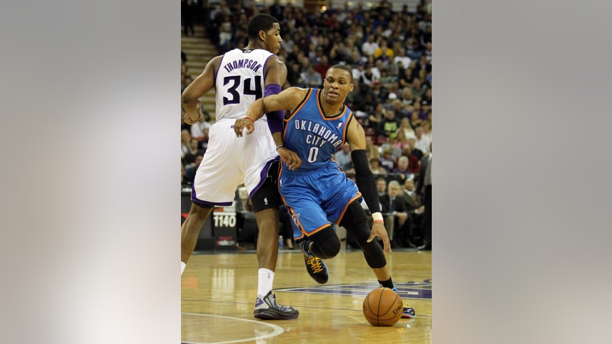 Oklahoma City Thunder guard Russell Westbrook, right, drives past Sacramento Kings forward Jason Thompson during the first quarter of  an NBA basketball game in Sacramento, Calif., Friday, Jan. 25, 2013. (AP Photo/Rich Pedroncelli)