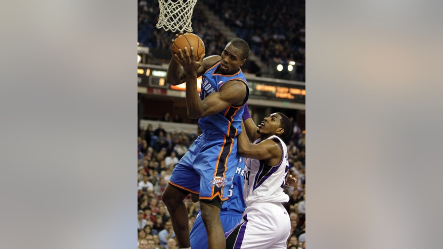 Oklahoma City Thunder center Serge Ibaka, top, of the Republic of Congo, left, grabs a rebound against Sacramento Kings forward Jason Thompson during the first quarter of  an NBA basketball game in Sacramento, Calif., Friday, Jan. 25, 2013. (AP Photo/Rich Pedroncelli)