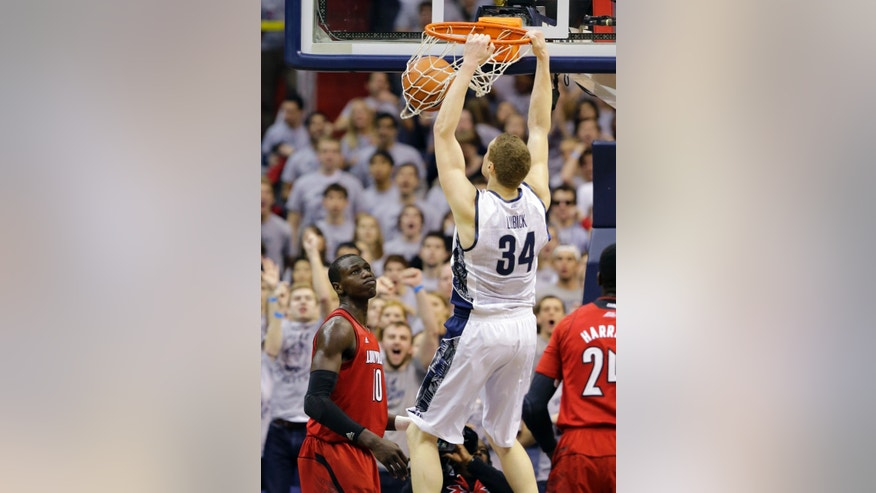 Georgetown forward Nate Lubick (34) dunks the ball in front of Louisville center Gorgui Dieng (10) during the first half of an NCAA college basketball game, Saturday, Jan. 26, 2013, in Washington. (AP Photo/Alex Brandon)