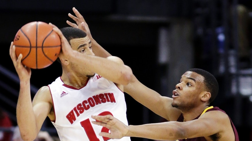 Minnesota's Andre Hollis, right, reaches in on Wisconsin's Traevon Jackson during the first half of an NCAA college basketball game, Saturday, Jan. 26, 2013, in Madison, Wis. (AP Photo/Andy Manis)