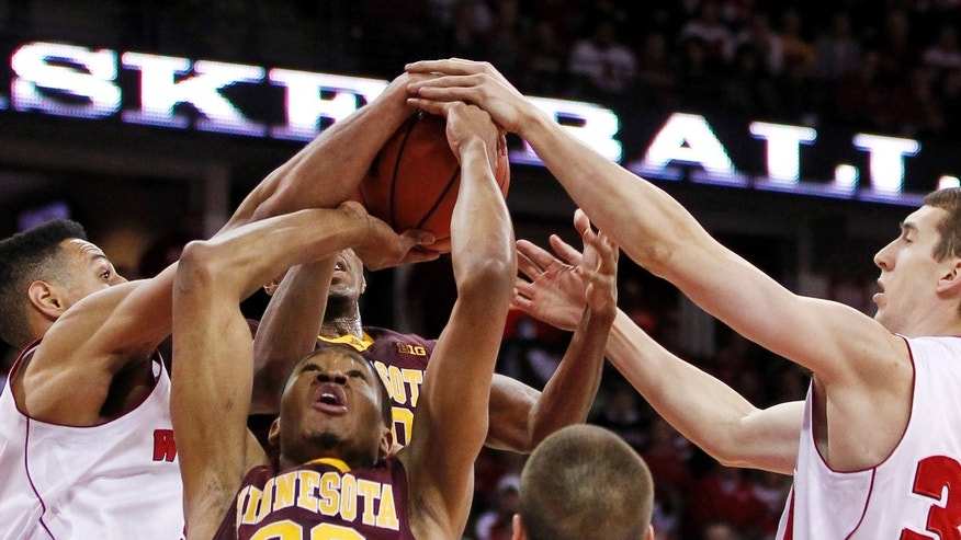 Wisconsin's Ryan Evans, left, and Zach Bohannon, right, battle with Minnesota's Rodney Williamns, bottom center, and Austin Hollis for possession of the ball during the first half of an NCAA college basketball game, Saturday, Jan. 26, 2013, in Madison, Wis. (AP Photo/Andy Manis)