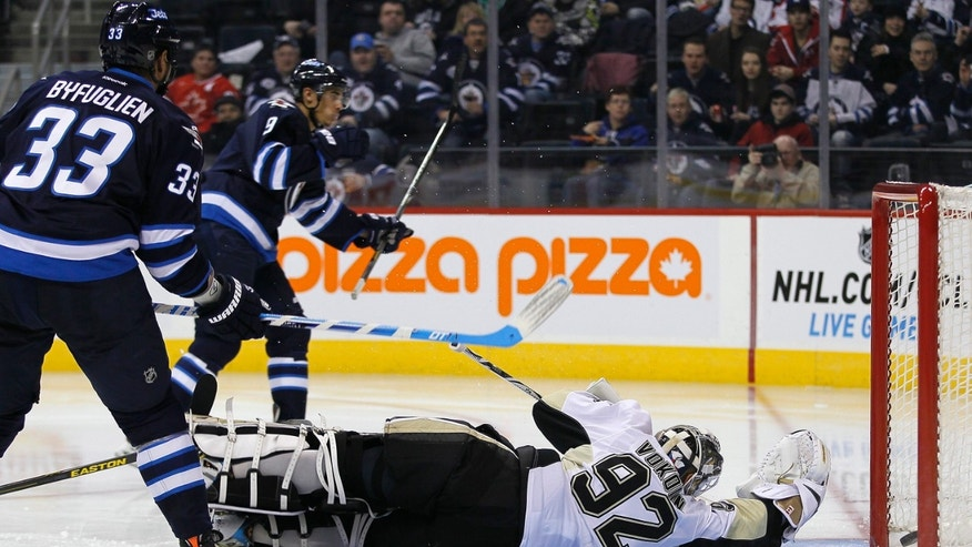 Winnipeg Jets' Evander Kane (9) scores on Pittsburgh Penguins' goaltender Tomas Vokoun (92) during second-period NHL hockey game action in Winnipeg, Manitoba, Friday, Jan. 25, 2013. (AP Photo/The Canadian Press, John Woods)