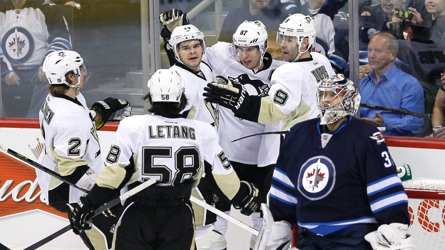 Pittsburgh Penguins' Sidney Crosby (87), Chris Kunitz (14), Pascal Dupuis (9), Matt Niskanen (2) and Kris Letang (58) celebrate Crosby's first goal against Winnipeg Jets goaltender Ondrej Pavelec during first-period NHL hockey game action in Winnipeg, Manitoba, Friday, Jan. 25, 2013. (AP Photo/The Canadian Press, John Woods)