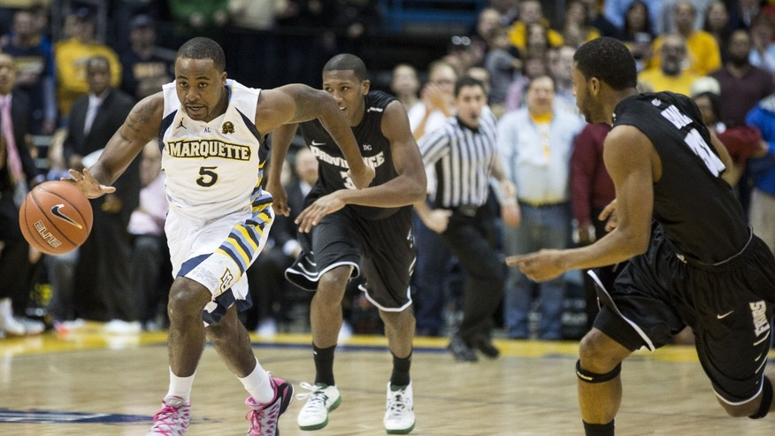 Marquette's Junior Cadougan (5) brings the ball up court as Providence's Vincent Council, right, and Kris Dunn chase during the first half of an NCAA college basketball game Saturday, Jan. 26, 2013, in Milwaukee. (AP Photo/Tom Lynn)