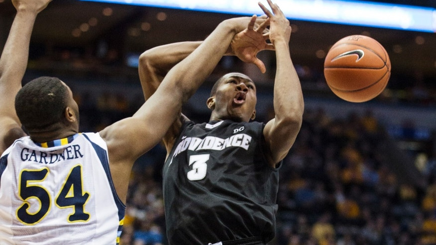 Marquette's Davante Gardner (54) fouls Providence's Kris Dunn during the second half of an NCAA college basketball game, Saturday, Jan. 26, 2013, in Milwaukee. (AP Photo/Tom Lynn)