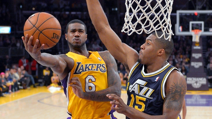 Los Angeles Lakers forward Earl Clark, left, puts up a shot as Utah Jazz forward Derrick Favors defends during the first half of an NBA basketball game, Friday, Jan. 25, 2013, in Los Angeles. (AP Photo/Mark J. Terrill)